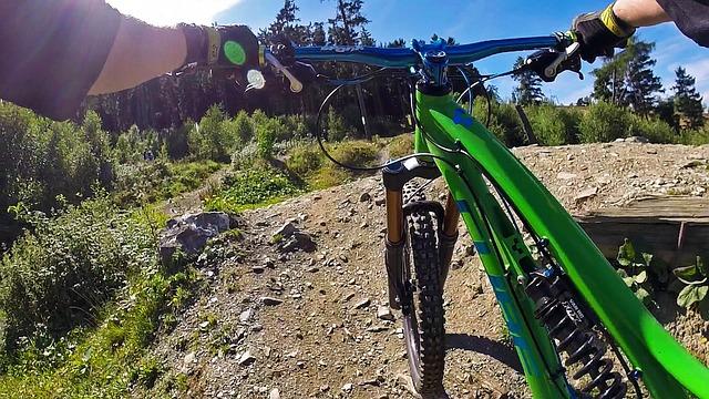 Na horském kole v terénu na kopci s výhledem na krajinu a lesy